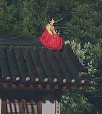Arang the ghost sits on a roof in brightly-colored Korean traditional dress;