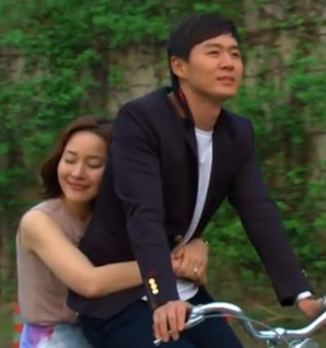 Uhm Ji Won rides behind Yun Jung Hun on a bicycle with her arms wrapped around him as he pedals happily;
