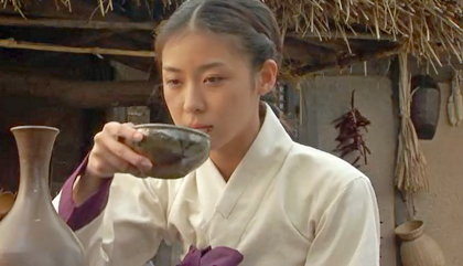 Damo Ha Ji Won, looking very unhappy, drinks from a stoneware bowl in front of a thatched cottage;