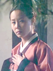 Chief Joh's daughter, watching unhappily as Chae Ohk and Hwangbo meet in the courtyard;