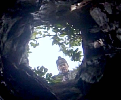 Hwangbo's head is framed by the hole in the ceiling of the cave as he calls down for Chae Ohk