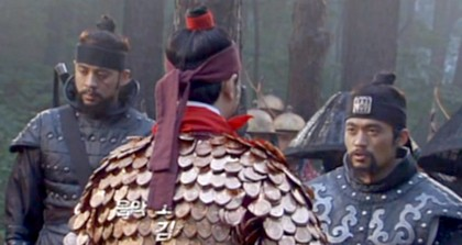 Hwangbo and the local commander debate authority while Officer Lee looks on in irritation