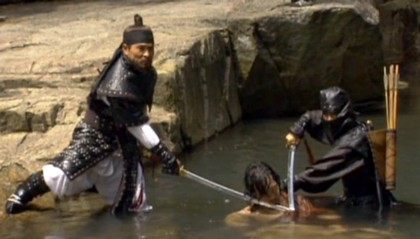 Officer Bael and an elite forces soldier hold their swords at the throat of the flating unconscious Jang Sung Baek