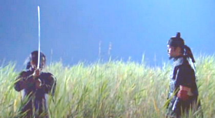 Hwangbo and the damo stand facing each other in a field of tall grass while Chae Ohk raises her sword
