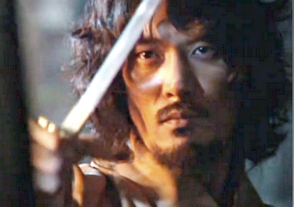 Jang Sung Baek looks grim and haunted as he raises his sword to the captive woman