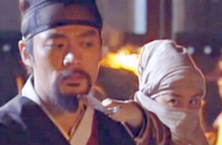Lee Seo Jin holds very still as Boss Jang's sidekick holds a sword at his throat;