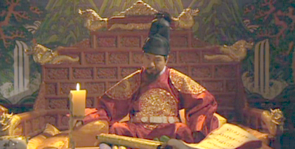 The King of Chosun sits cross-legged on a wide, cushioned throne, elaborately embellished and gilded, with a beautifully painted waterfall screen behind it;