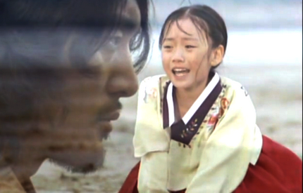 Boss Jang's brooding face in the foreground is superimposed over an image of his 7-tear old sister crying on the beach where they were separated as children;