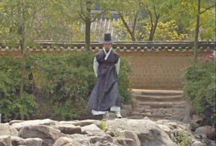 Lee Seo Jin crosses a stone dam, looking pensive.