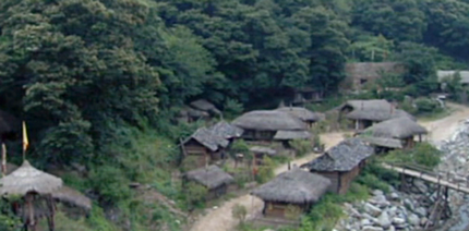 view from above of the thatched huts of the mountain rebel camp;