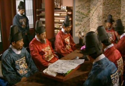 Richly dressed Lords are seated around a table while Hwangbo stands in the background against the wall;