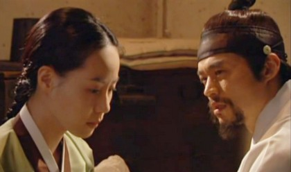 Nan Hui sits tearfully beside Hwangbo's bed as he asks her why she is doing this;