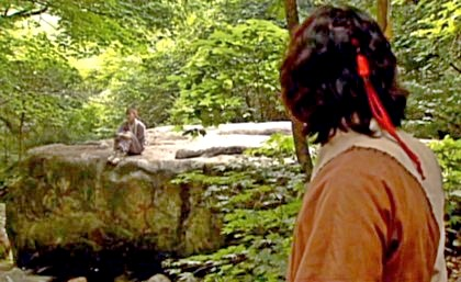 Chae Ohk sits on a rock in a beautiful green woods while Boss Jang watches her from a distance;