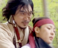 Chief Jang gallops back to camp at top speed holding a fainting Chae Ohk on the horse in front of him;