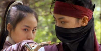 A masked Chae Ohkj glances sideway over her shoulder at Soo Myung who is holding a sword to her throat;