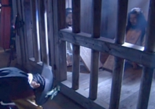 Commander Joh bows to the floor in front of his father and Hwangbo's jail cell;