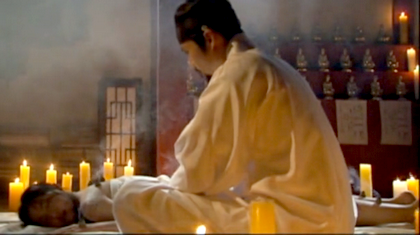 The damo lies covered with a sheet while Hwangbo tends smoking moxa cones on her back and limbs;