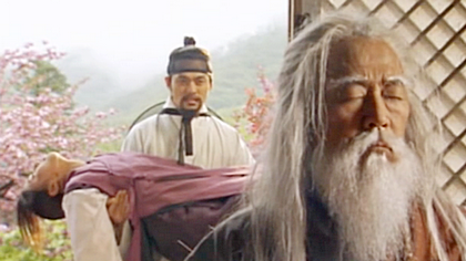 A monk with long white hair and bear meditates in the foreground as Hwangbo stands in the doorway with the unconscious damo;