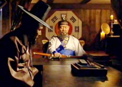 The Lord sits at the head of a table with the Korean flag behind him while the Magistrate reports on the planned raid of the leper village;