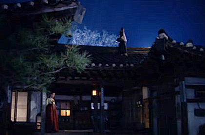 Nan Hui stands in front of her quarters in tears, looking into the darkness as Chae Ohk stands silently above her on the roof