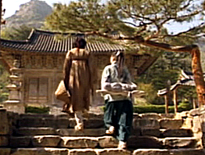 Damo 10 Boss Jang and Soo Myung climb steps towards a small building on the grounds of a mountain monastery