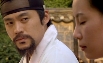 Hwangbo glares at Nan Hui as she kneels beside him with her eyes closed