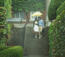 Yoona and Jang Geun Suk huddled together under a yellow umbrella walking across a leafy summer campus in the rain;