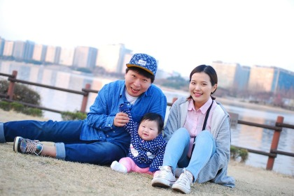 A Korean kajok consisting of a man, woman and baby sit in a park with a river and city buildings in the background