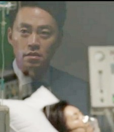 Lee Seo Jin's concerned face is reflected in the window as he looks into the hospital room where his mother is hooked up to monitors and IVs