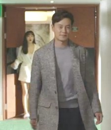 Lee Seo Jin walks down a hotel corridor grinning smugly and ignoring the calls of the woman he has just dumped from the doorway behind him