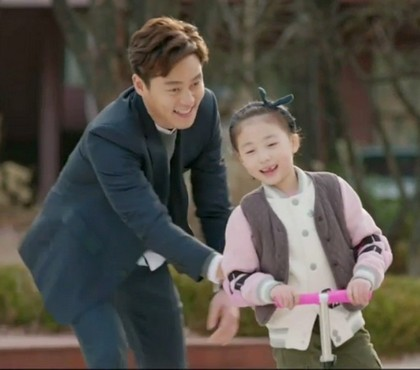 A laughing Lee Seo Jin steadies Shin Rin Ah as she races around the park on a scooter he bought for her