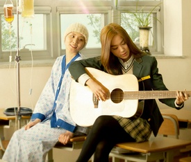 A young woman in a hospital gown with an IV looks on as  her sister in school clothes plays a guitar