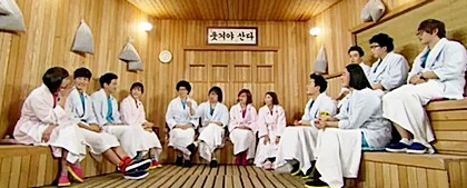 13 men and women in matching bathrobes sit on benches along the walls of a set that looks like a sauna