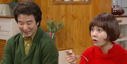 Hong Yo Seop as Choi Min Seok smiles as Ho Jeong stares at the TV in shock with her fork halfway to her mouth