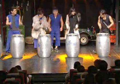 Ji Seon and Seo Young join a troop of drummers on stage beating on tall silver drums