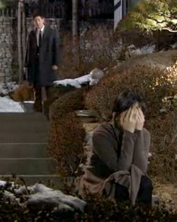 Seo Young sits on a step weeping, as Woo Jae looks on from behind her