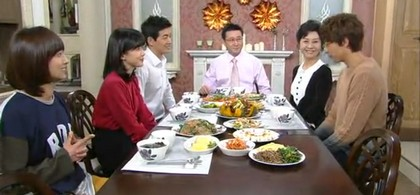 The Kang family sits smiling arund the breakfast table to welcome Seong Jae home