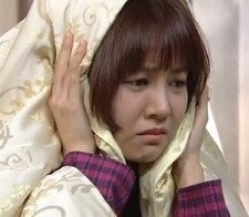 Ho Jeong presses her quilt to her ears to block out Sam Jae and Sang Woo's conversation