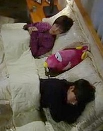 """""""Ho Jeong and Sang Woo lie on opposite sides of their bed with a large one-eyed pink stuffed animal between their pillows"""