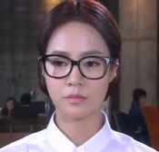 Choi Heo Joeng in a severe hairstyle with large black framed glasses and very plain dress