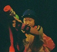 Nari points a colorful toy gun at the villain's tires