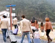 men and women arriving with suitcases at a rural resort