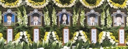 Close up of altar for victims of Sewolo ferry disaster showing photos of 5 students surrounded by floral arrangements
