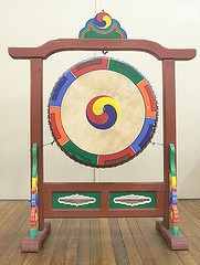 A brightly painted Korean drum or buk, hanging from a vertical wooden frame.