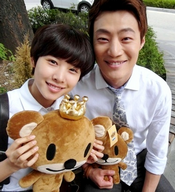 A smiling Lee Hee Joon sits close to Jo Yoon Hee, who is holding up a teddy bear;
