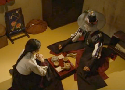Lee Seo Jin as Hwangbo and Ha Ji Won as Chae Ohk sit across from each other on the floor over a tiny tea table;