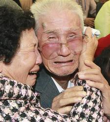 Photo of woman embracing crying elderly man