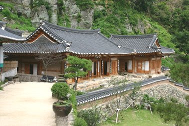 A well-kept hanok house in the country with a rocky mountain wall behind it