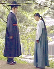 A man and woman wearing Joseon hanbok stand under a tree talking