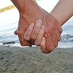 Clasped hands of two people on a beach